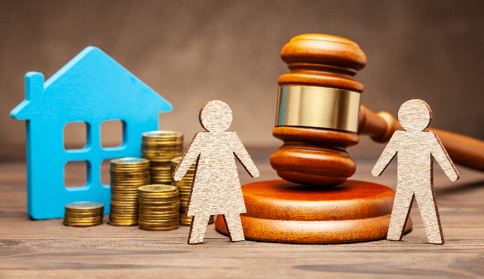 Due figure di legno di uomo e donna sono appoggiate su un tavolo, davanti ad un martelletto da giudice, una pila di monete e una casa di legno blu, ad indicare il divorzio tra due persone e l'assegno di mantenimento.