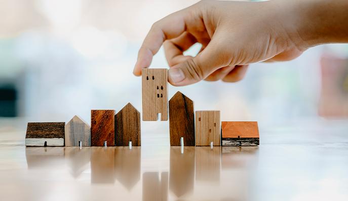 Mano scegliendo mini modello di casa in legno dal modello e fila di soldi moneta sul tavolo di legno, messa a fuoco selettiva, pianificazione di acquistare proprietà.