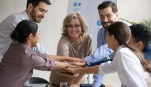 Un gruppo di persone appoggia le proprie mani sopra le altre per formare un team.